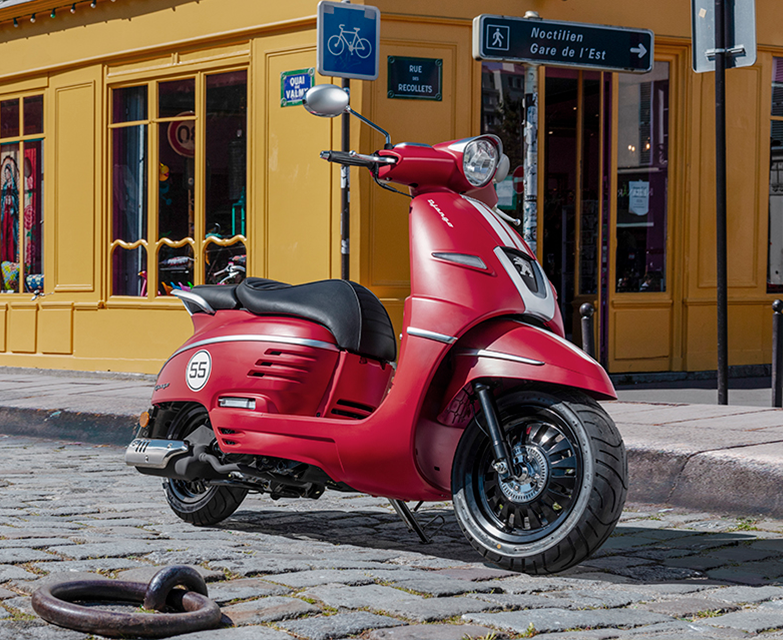 red and white Peugeot Django 150 scooter parked in a street