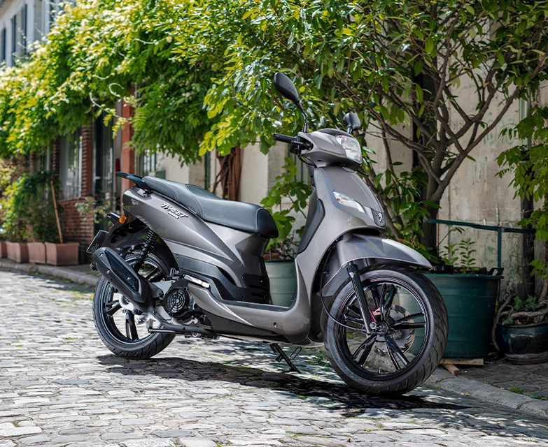 a grey peugeot tweet 125 scooter on its side stand in the streets